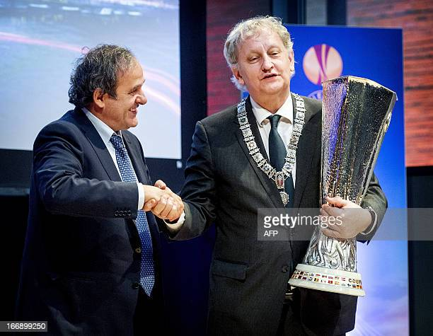 Mayor of Amsterdam Eberhard van der Laan receives from UEFA President Michel Platini the UEFA Europa League trophy on April 18, 2013 in Amsterdam,...