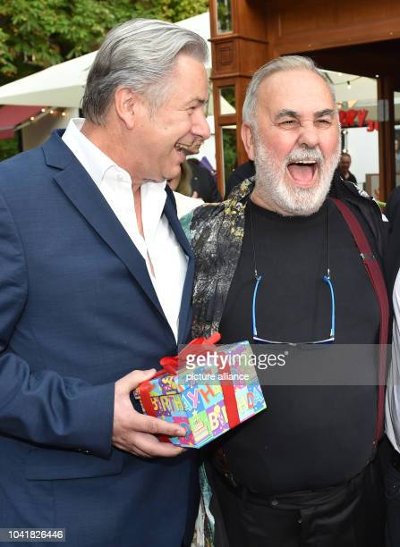 Mayor of Berlin Klaus Wowereit and celebrity hairdresser Udo Walz share a laugh at the party for Walz's 70th birthday at 'Bar jeder Vernunft' in...