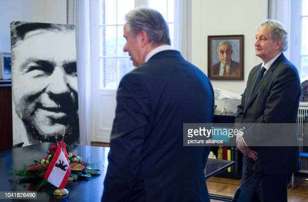 Mayor of Berlin Klaus Wowereit shows Mayor of Amsterdam Eberhard van der Laan stand in the front of a portrait of Wowereit in city hall in Berlin...
