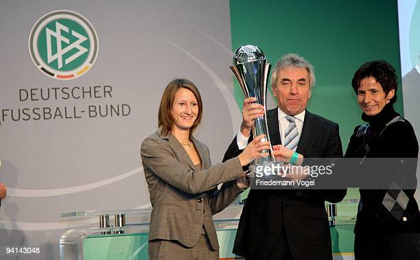 Mayor of Cologne Juergen Roters receives the trophy from Sonja Fuss and Bettina Wiegmann during the German Football Association women trophy...