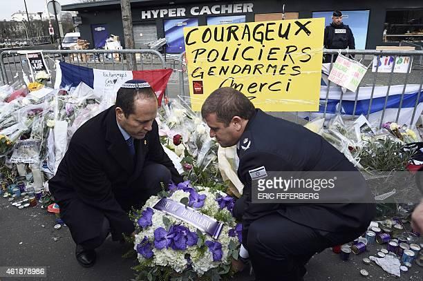Mayor of Jerusalem Nir Barkat and Police Chief of Jerusalem Moshe Edry place flowers in front of the Hyper Cacher kosher supermarket in Paris on...