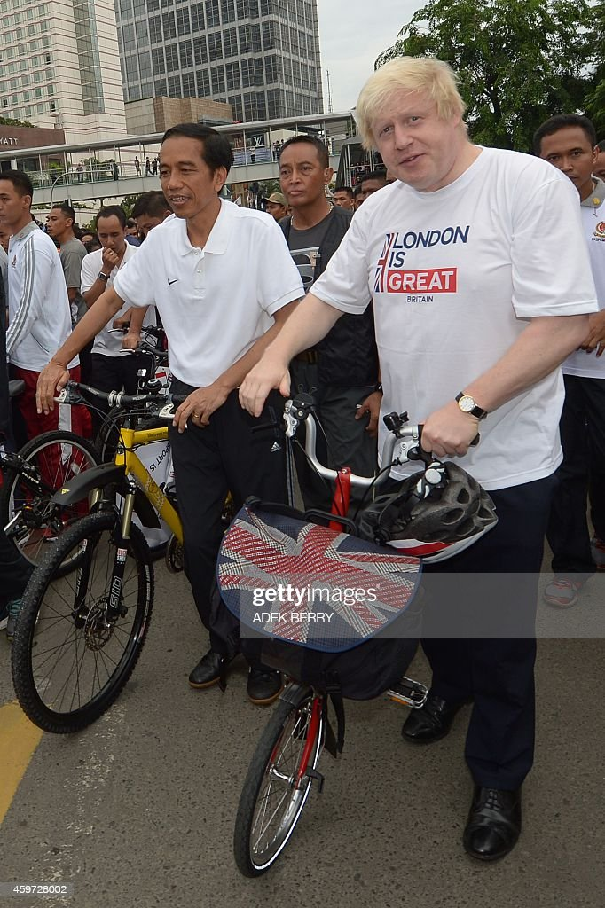 Mayor of London Boris Johnson (R) and Indonesia's President Joko Widodo (L) walk with their bikes in Jakarta on November 30, 2014. Johnson will build on his work to create jobs and growth, and promote London to the world as a major investment destination as he leads a trade mission to Singapore, Kuala Lumpur and Jakarta.
