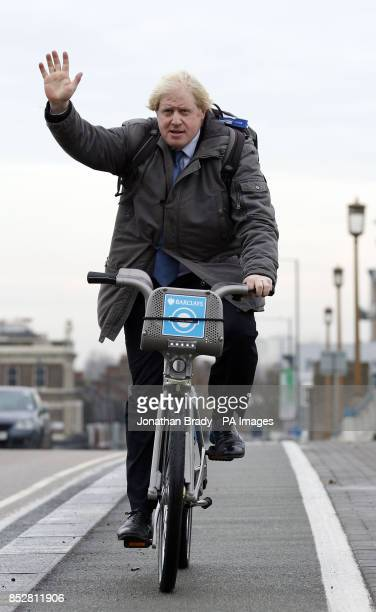 Mayor of London Boris Johnson cycles across Wandsworth Bridge at the launch of the expansion of the Barclays Cycle Hire scheme to Wandsworth Town...