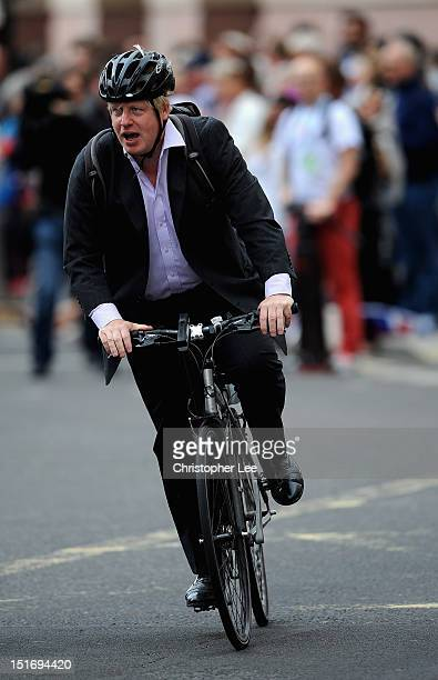 Mayor of London Boris Johnson cycle's along the parade route ahead of the London 2012 Victory Parade for Team GB and Paralympic GB athletes on...