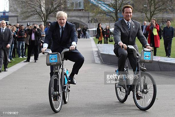 Mayor of London Boris Johnson cycles London Cycle Hire bikes with former Governor of California Arnold Schwarzenegger in front of City Hall on March...