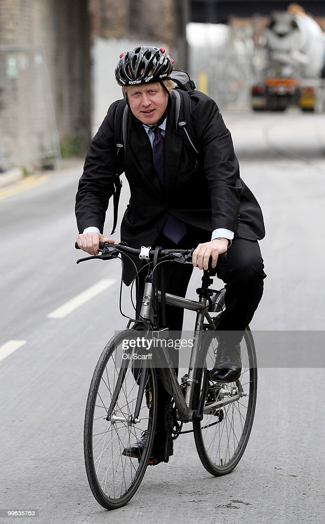Mayor of London Boris Johnson departs on his bicycle after attending a press conference to announce the design for London's new Routemaster bus, in Battersea Bus Depot on May 17, 2010 in London, England. The new double-decker buses, which will feature a rear open platform enabling people to 'hop-on hop-off', are claimed to be 40% more fuel efficient than current London buses and are due to go into service in 2011.