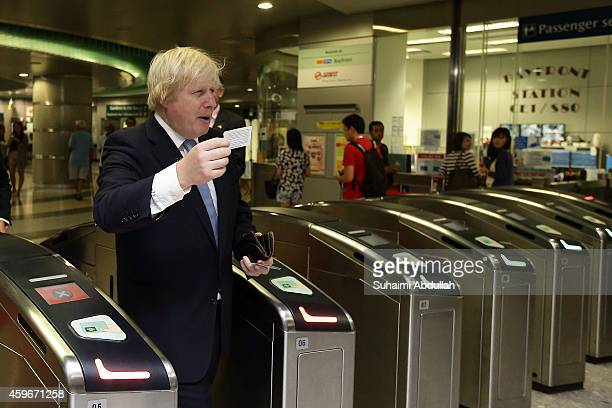 Mayor of London Boris Johnson enters the ticketing gantry of the Singapore underground mass rapid system after attending the FinTech event at the...