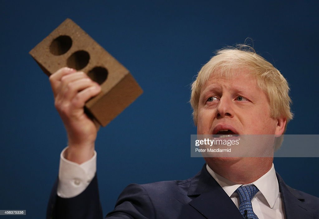 Mayor of London Boris Johnson holds a house brick aloft as he addresses the Conservative party conference on September 30, 2014 in Birmingham, England. The third day of conference will see speeches on home affairs and justice.