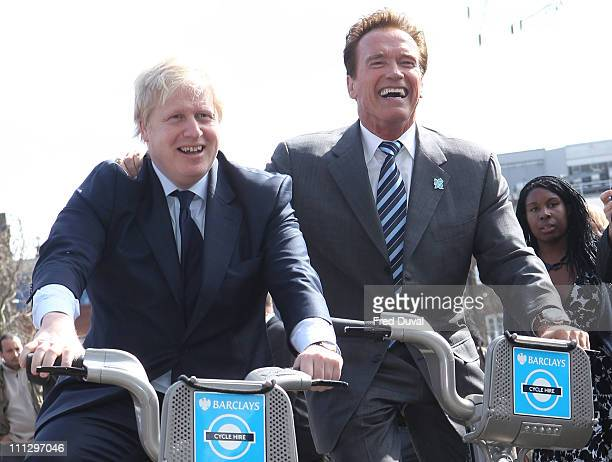 Mayor of London Boris Johnson poses on London Cycle Hire bikes with former Governor of California Arnold Schwarzenegger in front of City Hall on...