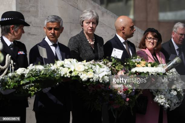 Mayor of London Sadiq Khan Britain's Prime Minister Theresa May and Britain's Home Secretary Sajid Javid hold floral tributes during a commemoration...