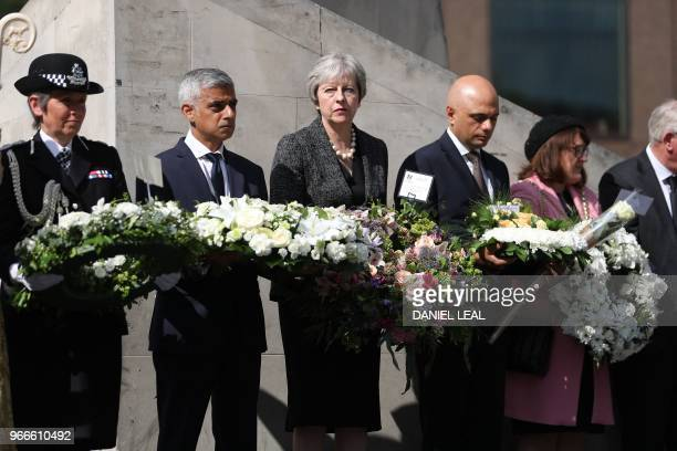 TOPSHOT Mayor of London Sadiq Khan Britain's Prime Minister Theresa May and Britain's Home Secretary Sajid Javid hold floral tributes during a...