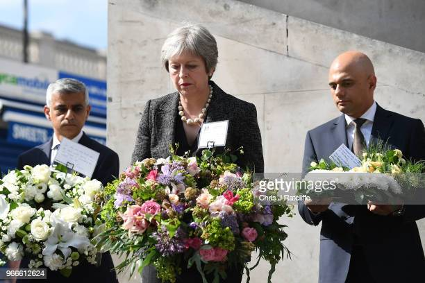 Mayor of London Sadiq Khan British Prime Minister Theresa May and Sajid Javid the British Home Secretary prepare to lay flowers after the minute's...