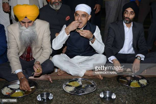 Mayor of London Sadiq Khan eats a communal vegetarian meal along with members of the Sikh community during his visit to the Golden Temple in Amritsar...