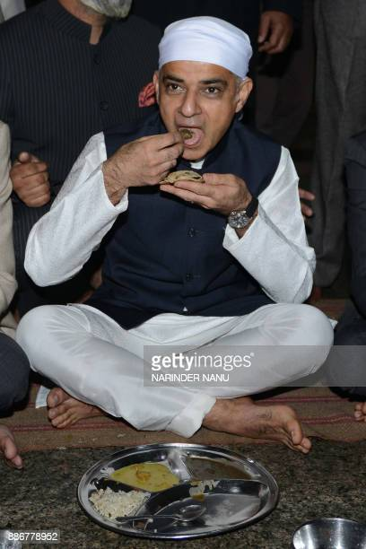 Mayor of London Sadiq Khan eats a communal vegetarian meal during his visit to the Golden Temple in Amritsar on December 62017 / AFP PHOTO / NARINDER...