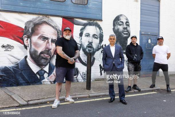 Mayor of London Sadiq Khan poses for a photo with artists Mr Meana , Gnasher and Murwalls owner Marc Silver in front of a new mural honouring members...