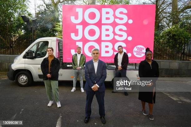 """Mayor of London Sadiq Khan poses for photographers in front of a poster stating his Mayoral campaign pledge of """"Jobs Jobs Jobs"""" on March 30, 2021 in..."""