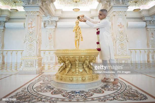 Mayor of London Sadiq Khan pours holy water over a statue of Swami Narayan during a visit to Akshardham Temple in Delhi as part of his fourday trip...