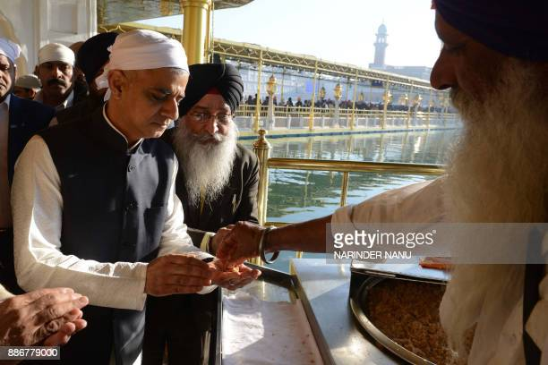 Mayor of London Sadiq Khan receives a traditional sweet from a member of the Sikh community during his visit to the Golden Temple complex in Amritsar...