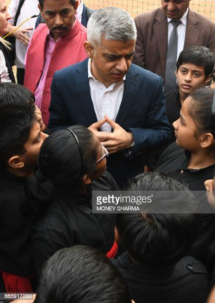 Mayor of London Sadiq Khan talks with school children during an event in a school in New Delhi on December 5 2017 Khan was in the Indian capital to...