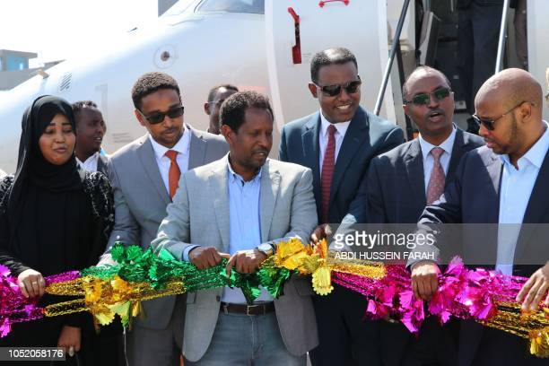 Mayor of Mogadishu Abdirahman Omar Osman and CEO of Ethiopias National Airways Abera Lemi celebrate after the first commercial flight by National...