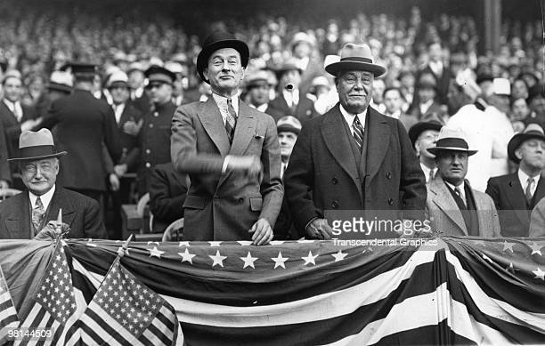 Mayor of New York City Jimmy Walker throws out the first ball of the 1923 season in Yankee Stadium, with team President Jacob Ruppert standing to his...