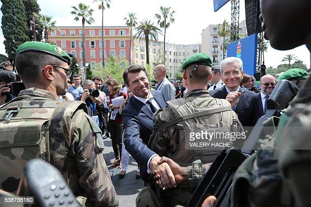 Mayor of Nice Christian Estrosi and Adolphe Colrat prefet of the Alpes Maritimes shakes hands with soldiers as he visits the fan zone in Nice...