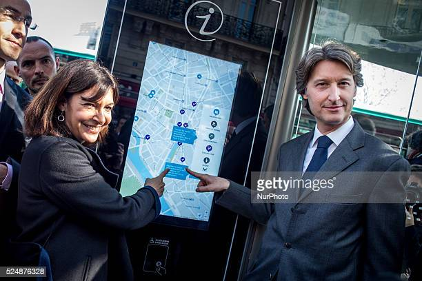 Mayor of Paris Anne Hidalgo and JeanCharles Decaux chairman of the board and coCEO of multinational advertising corporation JCDecaux test out a touch...