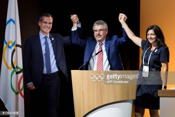 Mayor of Paris Anne Hidalgo International Olympic Committee President German Thomas Bach and Los Angeles Mayor Eric Garcetti reacts on the podium...