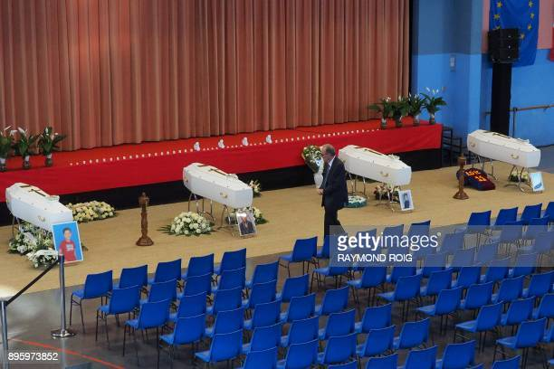 Mayor of Saint Feliu d'Avall Robert Taillant walks by coffin of victims killed in a collision between a train and a school bus on December 20 2017 in...