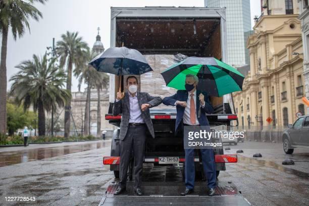 Mayor of Santiago de Chile Felipe Alessandri and Chargé d'Affaires in Santiago de Chile Baxter Hunt pose next to a truck with 450 boxes of food...