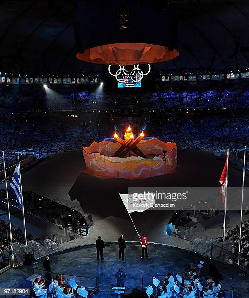 Mayor of Vancouver Gregor Robertson passes the Olympic flag to IOC President Jacques Rogge as Mayor of Sochi Anatoly Pakhomov looks on during the...