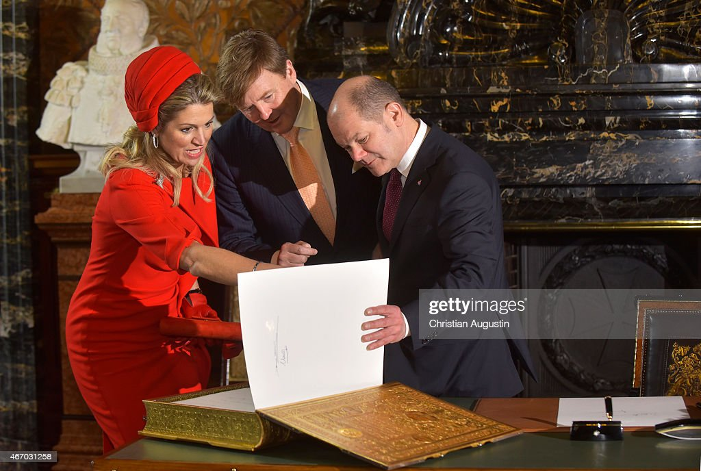 Mayor Olaf Scholz shows Queen Maxima and King Willem-Alexander of The Netherlands the signature of the parents (Queen Beatrix and Prince Claus) of King Willem-Alexander in the golden book of the city of Hamburg at the townhall of Hamburg on March 20, 2015 in Hamburg, Germany.