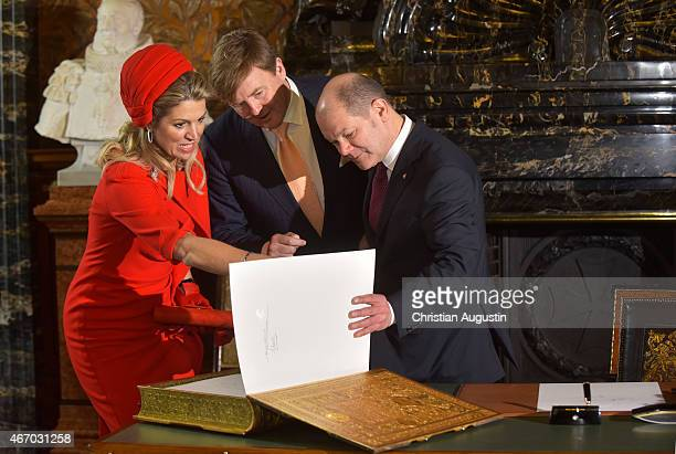 Mayor Olaf Scholz shows Queen Maxima and King WillemAlexander of The Netherlands the signature of the parents of King WillemAlexander in the golden...