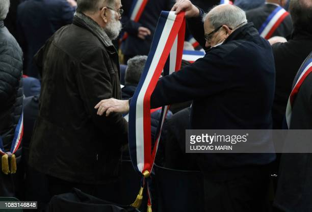 A mayor puts on a sash with the French national colours as he attends a meeting gathering some 600 mayors who will relay the concerns aired by...