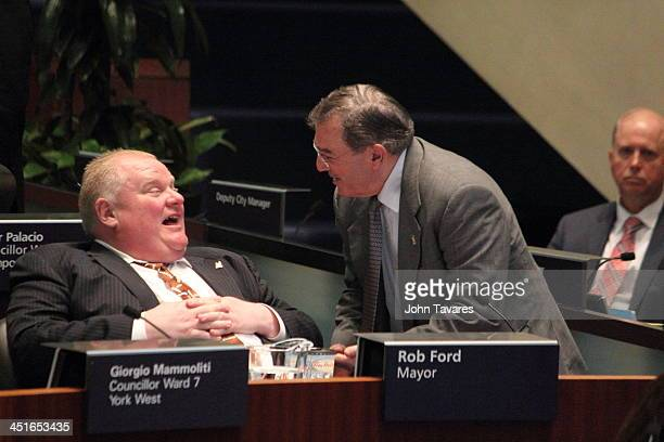 Mayor Rob Ford chats with Councillor Frank Di Giorgio during a city council meeting after he had made controversial remarks to the press about oral...