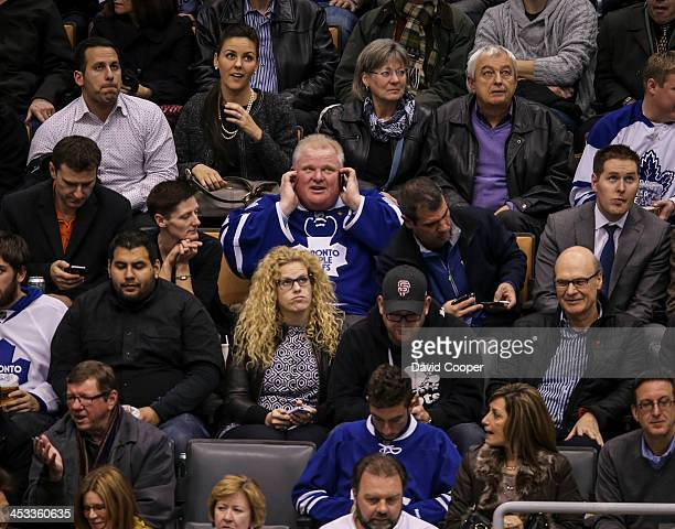 TORONTO ON DECEMBER 3 Mayor Rob Ford talks on his cell phone as he sitting in the seats behind the San Jose Sharks bench the 3rd period as the...