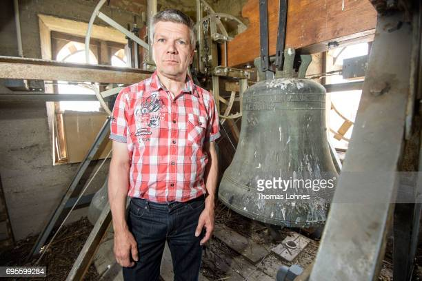 Mayor Ronald Becker stands next to the church bell embossed with a swastika and the text 'Everything for the Fatherland Adolf Hitler' in the...