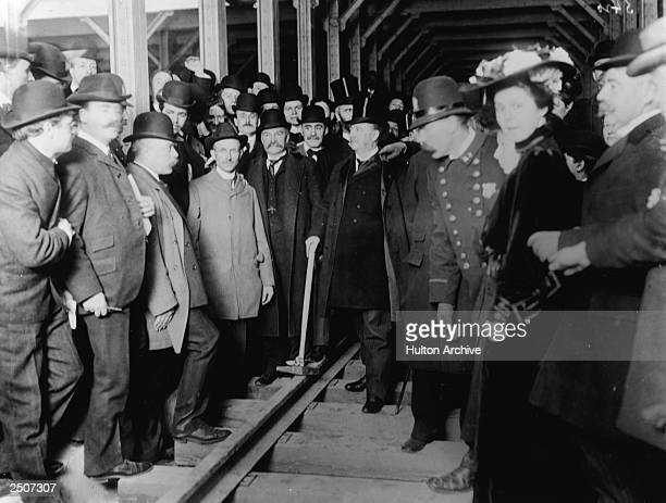 Mayor Seth Low holds a mallet surrounded by a crowd of police officials and citizens at a dedication ceremony for a New York City subway station...