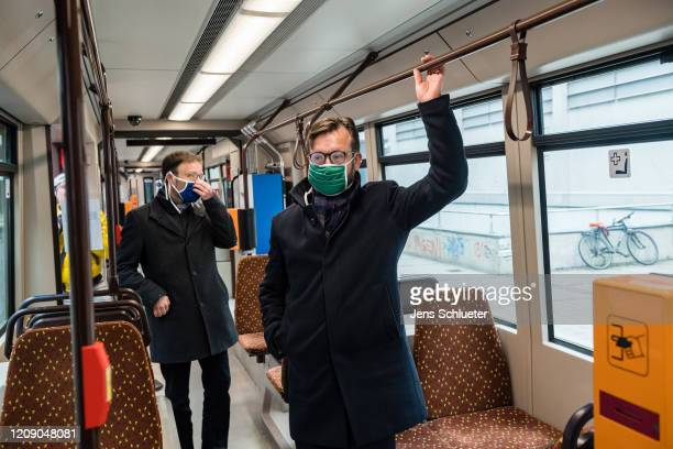 Mayor Thomas Nitzsche and Steffen Gundermann managing director of the Jena public transport company demonstrate wearing a protective face mask in a...