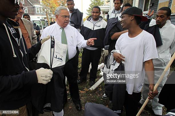Mayor Tom Menino chats with J'Shaun Reddick a part of local youth group the Mayors Clean Team that help the City maintain foreclosed properties that...