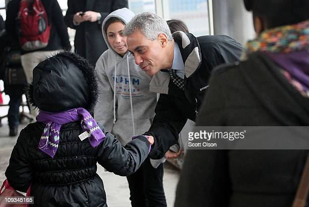 Mayoral candidate Rahm Emanuel greets commuters with his daughter Ilana at an L train station while campaigning February 22 2011 in Chicago Illinois...