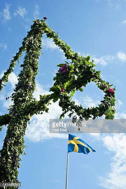 Maypole and Swedish flag against sky
