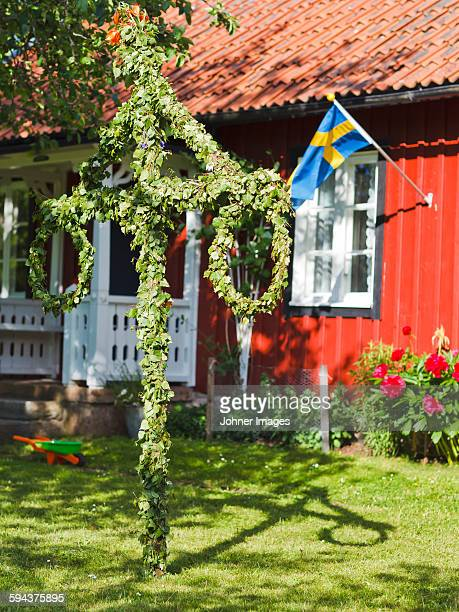Maypole in front of wooden house