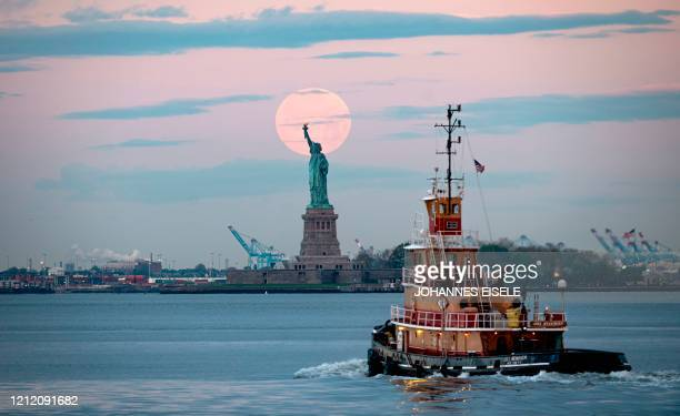 TOPSHOT May's full Moon known as the Full Flower Moon and is the last supermoon of the year sets behind the Statue of Liberty on May 7 2020 in New...