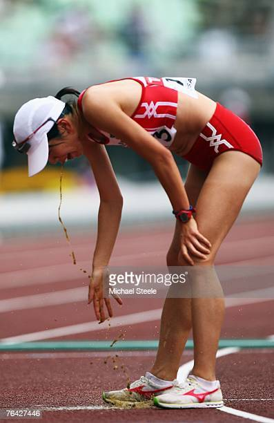 Mayumi Kawasaki of Japan vomits after she crosses the finish line during the Women's 20k Race Walk Final on day seven of the 11th IAAF World...
