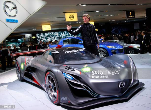 Mazda design director of Mazda North American operations Franz von Holzhausen motions to executives to join him as he poses with the Furai concept...