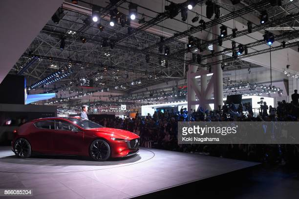 Mazda Motor Co CEO Masamichi Kogai poses with Mazda Kai Concept during a press conference at the Mazda Motor Co booth during the Tokyo Motor Show at...