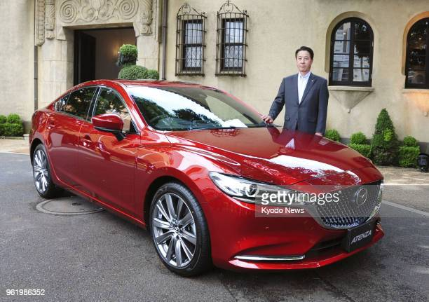 Mazda Motor Corp President and CEO Masamichi Kogai poses with a revamped model of the Atenza sedan in Tokyo on May 24 2018 ==Kyodo