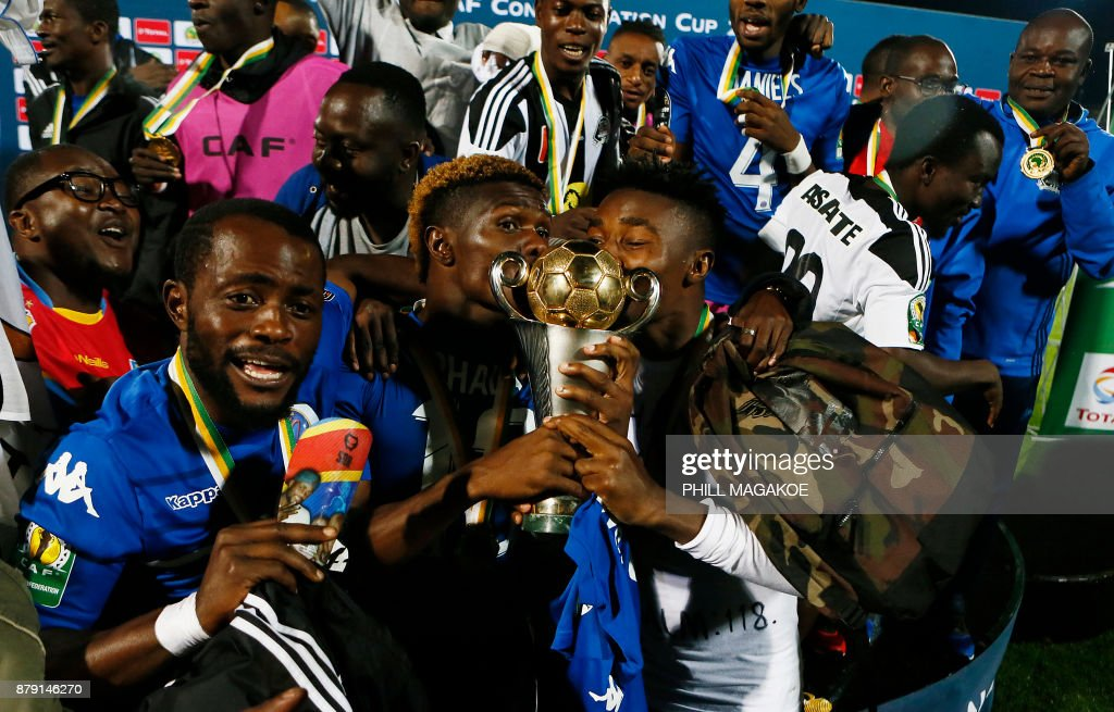 TP Mazembe players celebrate with the trophy their victory over Supersport United in the final football match of the CAF Confederation trophy at Lucas Moripe stadium in Atteridgeville on November 25, 2017 in Pretoria. /