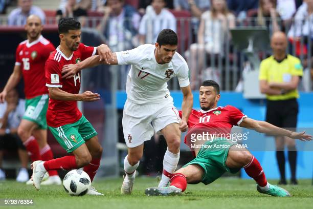 Mbark Boussoufa and Younes Belhanda of Morocco challenge Goncalo Guedes of Portugal during the 2018 FIFA World Cup Russia group B match between...